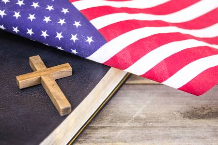 93338296-an-american-flag-with-a-wooden-christian-cross-and-a-holy-bible-on-a-wood-background-